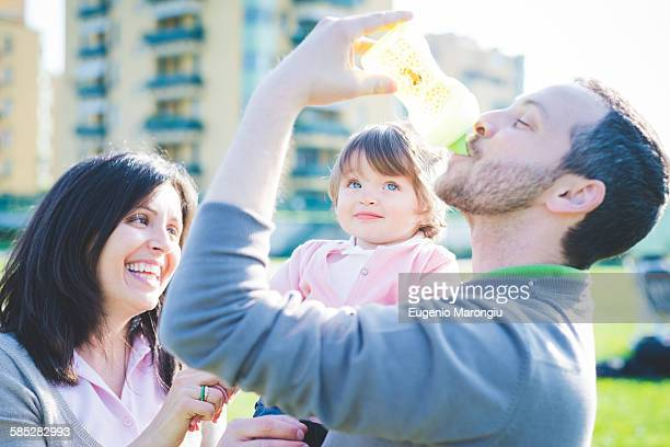 Mid adult man drinking toddler daughters baby bottle in park