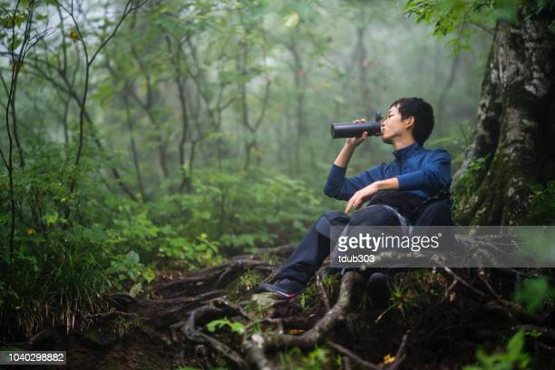 mid adult man drinking water while hiking - tottori prefecture stock pictures, royalty-free photos & images