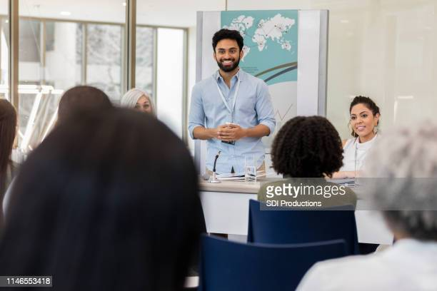 mid adult man eagerly answers questions - summit meeting stock pictures, royalty-free photos & images