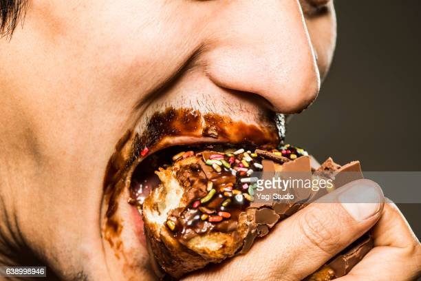 mid adult man  eating a donut,close up shot - gier stock-fotos und bilder