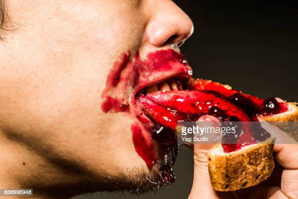 mid adult man eating strawberry jam toast,close up shot - gier stock-fotos und bilder