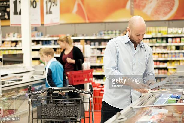 Mid adult man examining product with family in background in grocery store