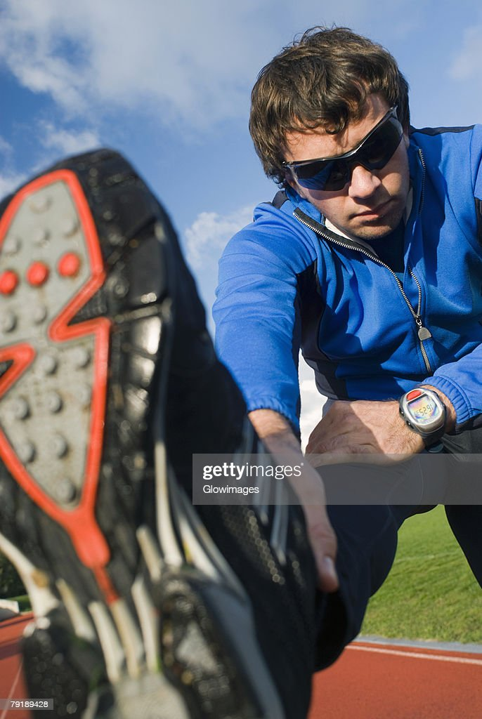 Mid adult man exercising on a running track : Foto de stock