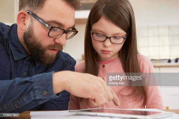 Mid adult man explaining homework to daughter at table