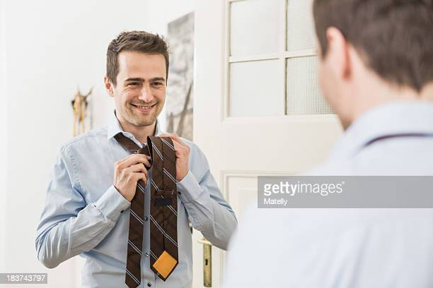 Mid adult man fastening tie in mirror