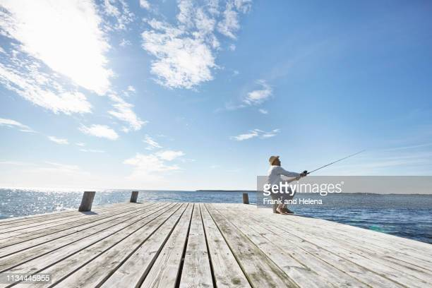 mid adult man fishing off pier, utvalnas, sweden - molo foto e immagini stock