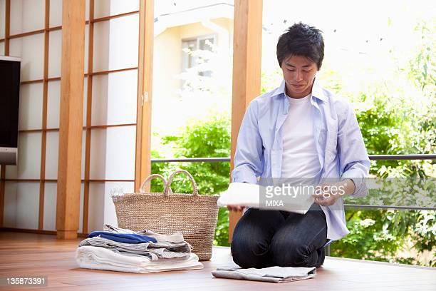 Mid adult man folding laundry