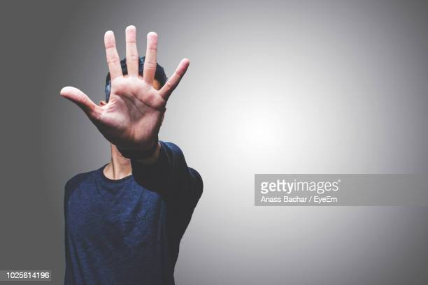 mid adult man gesturing while standing against gray background - stop sign stock pictures, royalty-free photos & images