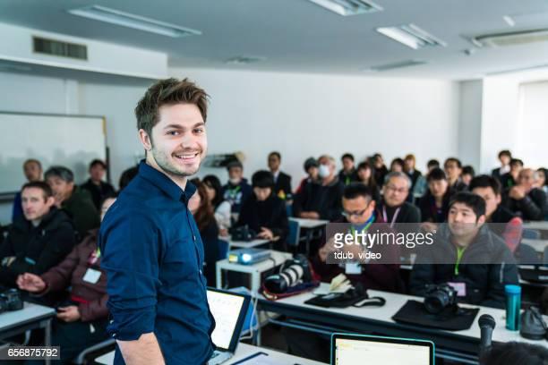 30 代の男性の人々 の大規模なグループにプレゼンテーションやスピーチを与えること