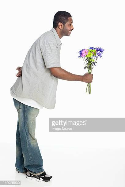 Mid Homme adulte donnant des fleurs sur fond blanc