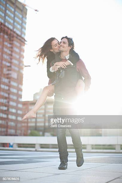 Mid adult man giving girlfriend piggyback on rooftop parking lot
