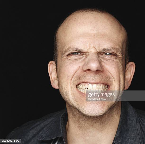 mid adult man gritting teeth, close-up, portrait - clenching teeth stock pictures, royalty-free photos & images