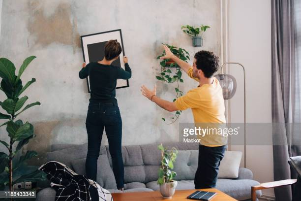 mid adult man guiding girlfriend in hanging picture frame on wall at new home - hausdekor stock-fotos und bilder
