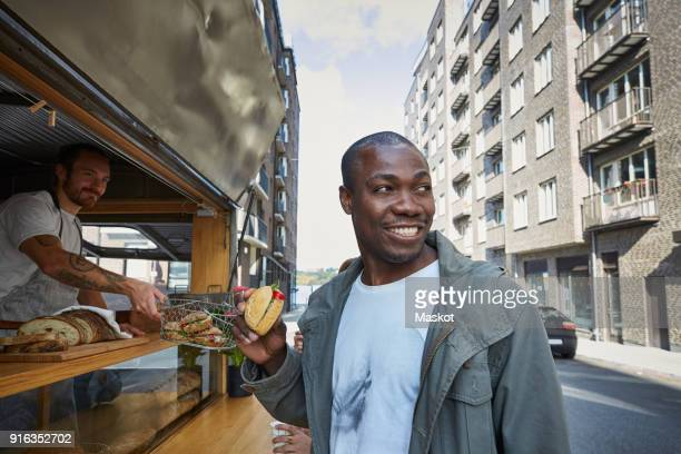 Mid adult man having burger while standing at food truck in city