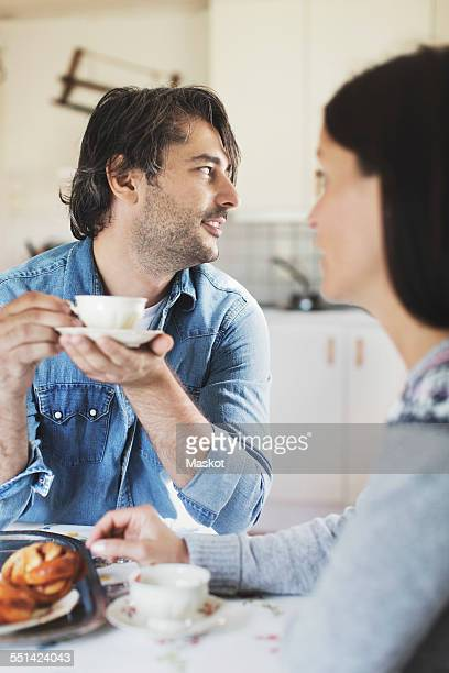 Mid adult man having coffee with woman at breakfast table