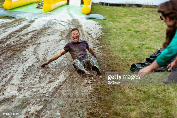 mid adult man having fun on muddy slip and slide - sports stock pictures, royalty-free photos & images