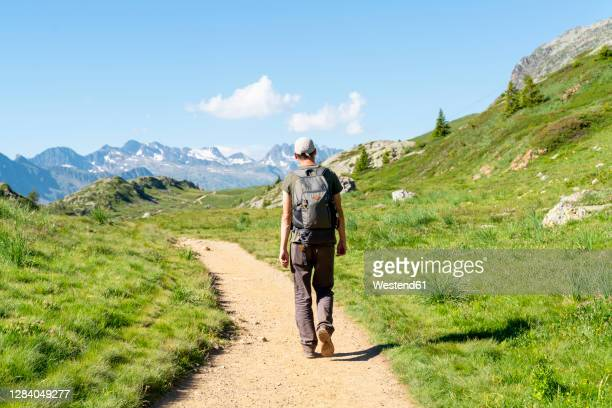 mid adult man hiking in mountain on sunny day - イゼール県 ストックフォトと画像