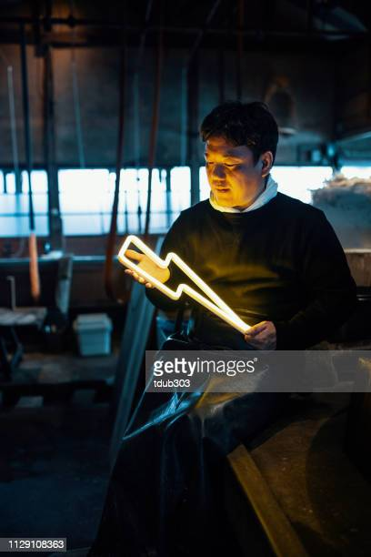 mid adult man holding an illuminated lightning bolt shaped neon light in a factory setting - dedication stock pictures, royalty-free photos & images