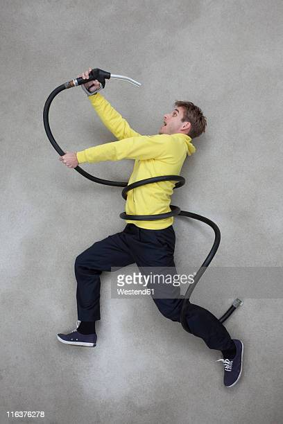 Mid adult man holding and looking shockly at hose
