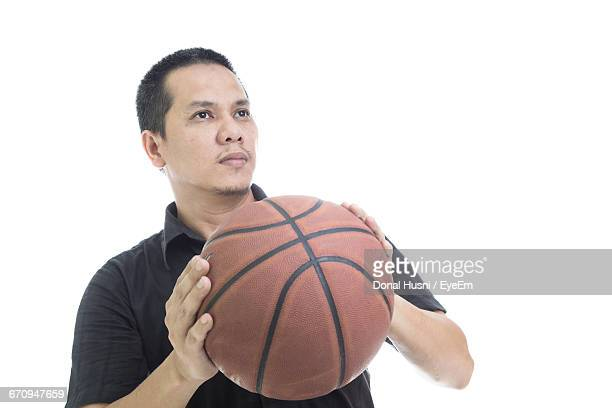 Mid Adult Man Holding Basketball Against White Background