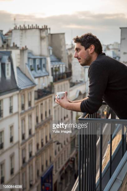 mid adult man holding coffee cup while leaning on balcony railing  paris  france - veiligheidshek stockfoto's en -beelden