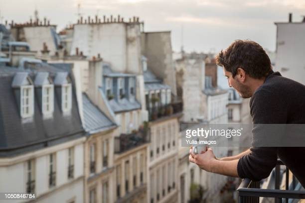 mid adult man holding coffee cup while leaning on balcony railing  paris  france - balcony stock pictures, royalty-free photos & images