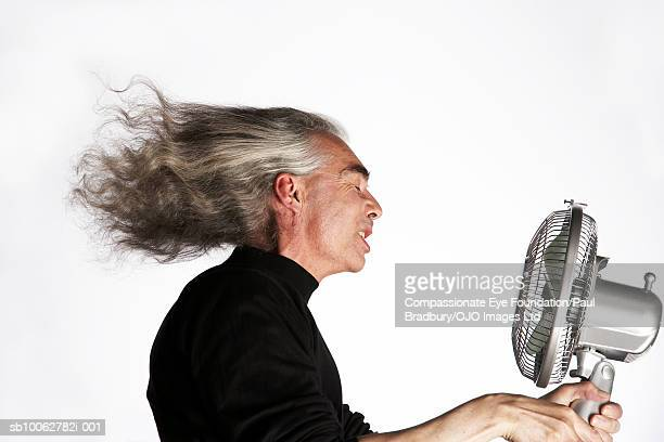 Mid adult man holding electric fan in front of face, side view