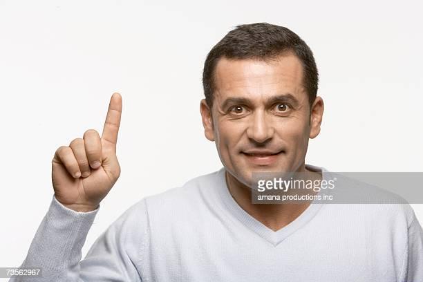 Mid adult man holding index finger up