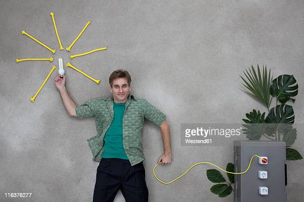 Mid adult man holding lighbulb and wire connected to socket