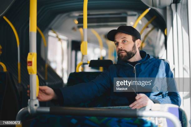 Mid adult man holding mobile phone while sitting in bus on sunny day