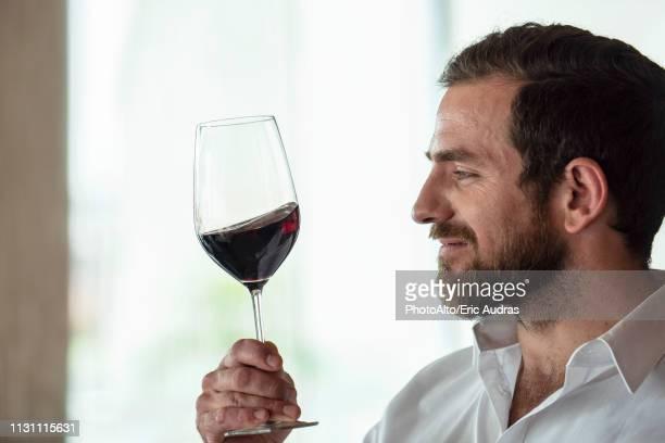 mid adult man holding red wine glass - 充足感 ストックフォトと画像