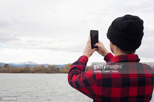 Mid adult man holding smart phone, taking photograph of view, rear view