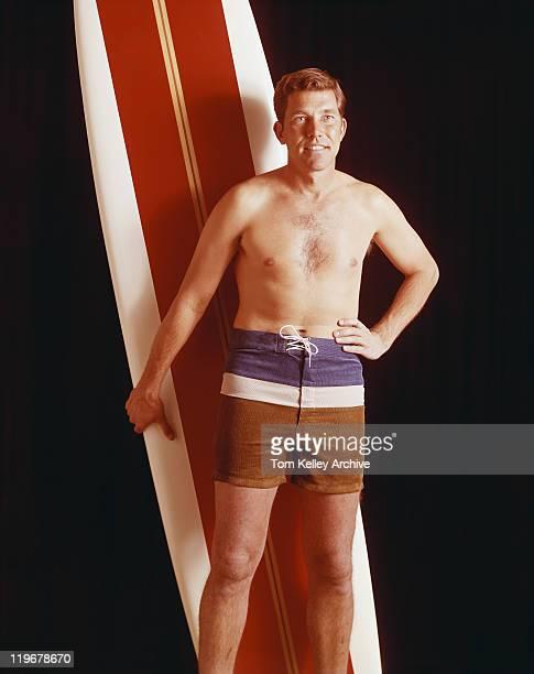 Mid adult man holding surfboard against black background