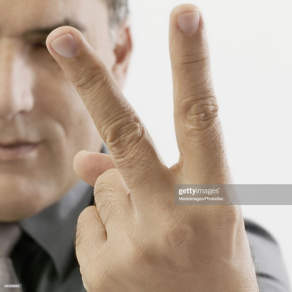 Mid Adult man holding two fingers out in peace sign : Stock Photo