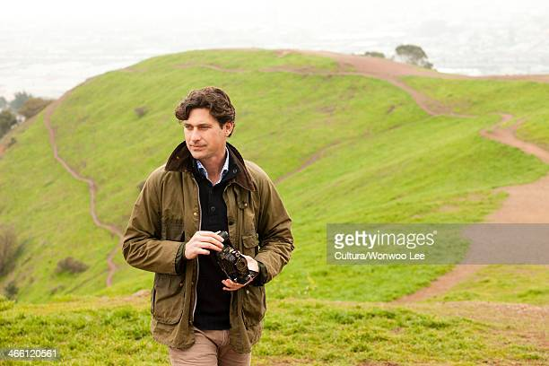 mid adult man holding vintage camera in countryside, looking away - mid adult men stock pictures, royalty-free photos & images