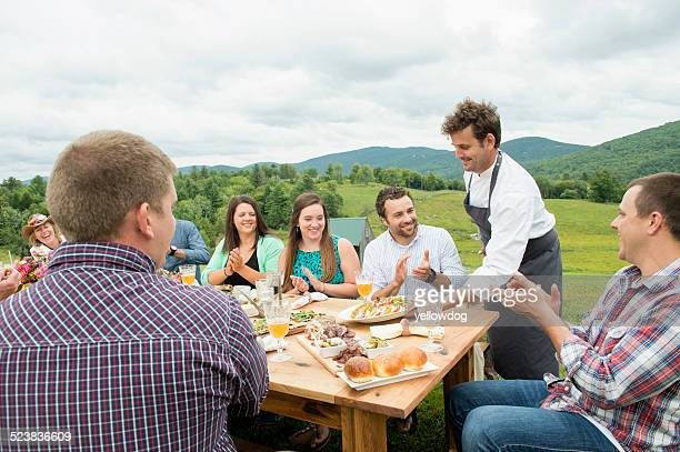 Mid adult man in apron, serving plate of food to family members at table, outdoors