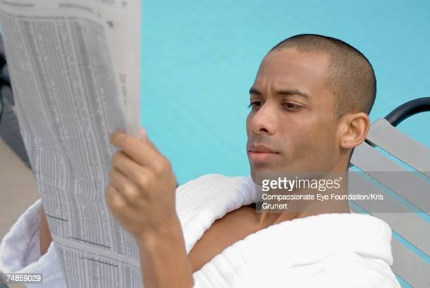 Mid adult man in bathrobe, reading newspaper at swimming pool