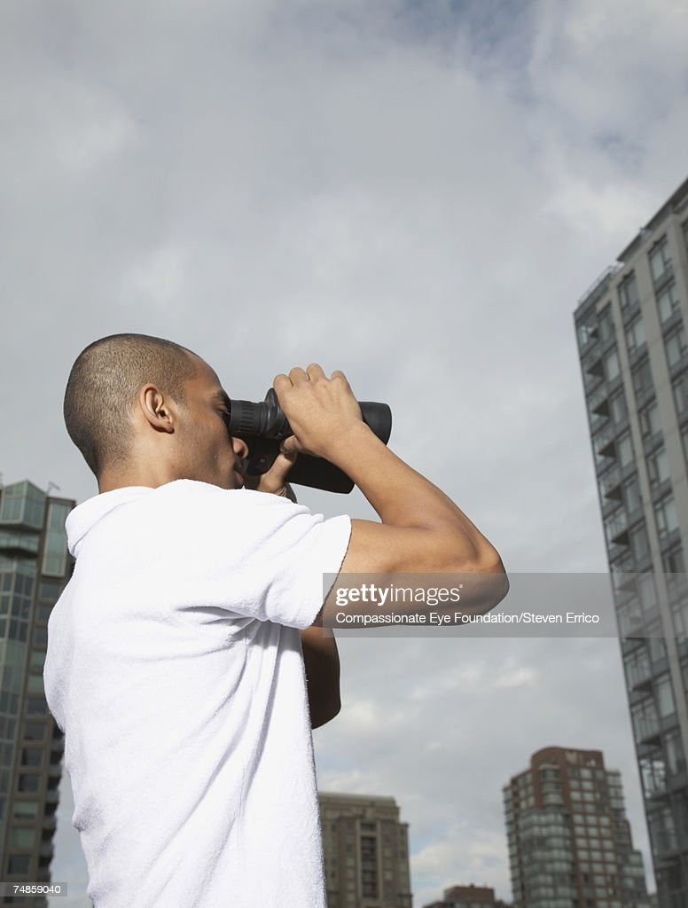 Mid adult man in city, using binoculars, low angle view : Stock Photo