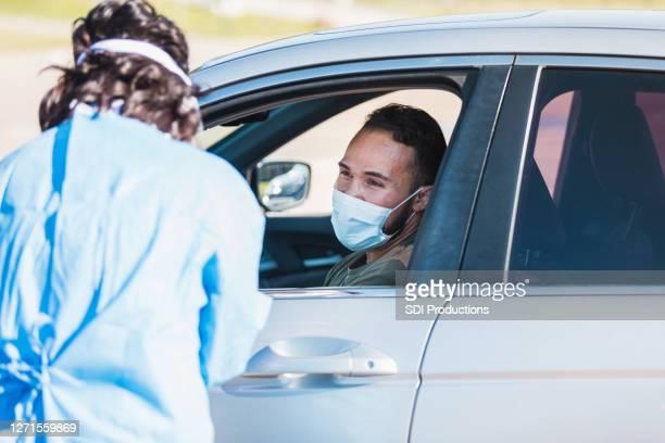 運転席の中年成人男性が医療従事者と話す - ドライブスルー検査 ストックフォトと画像