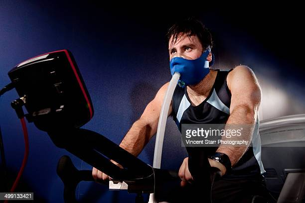 Mid adult man in face mask on gym exercise cycle in altitude centre