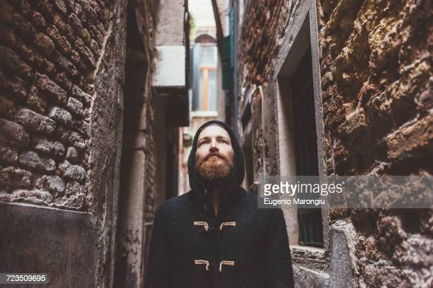 mid adult man in hooded duffle coat staring from alley, venice, italy - ダッフルコート ストックフォトと画像