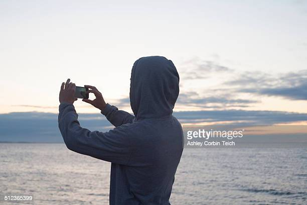 Mid adult man in hooded top photographing sea with smartphone, Gloucester, Massachusetts, USA