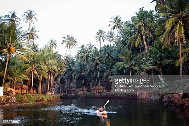 Mid adult man in kayak, paddling down river, Goa, India
