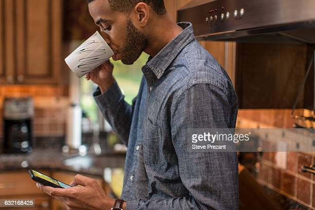 Mid adult man in kitchen reading smartphone text and drinking coffee