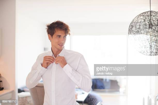 mid adult man in living room buttoning shirt - preparation stock-fotos und bilder
