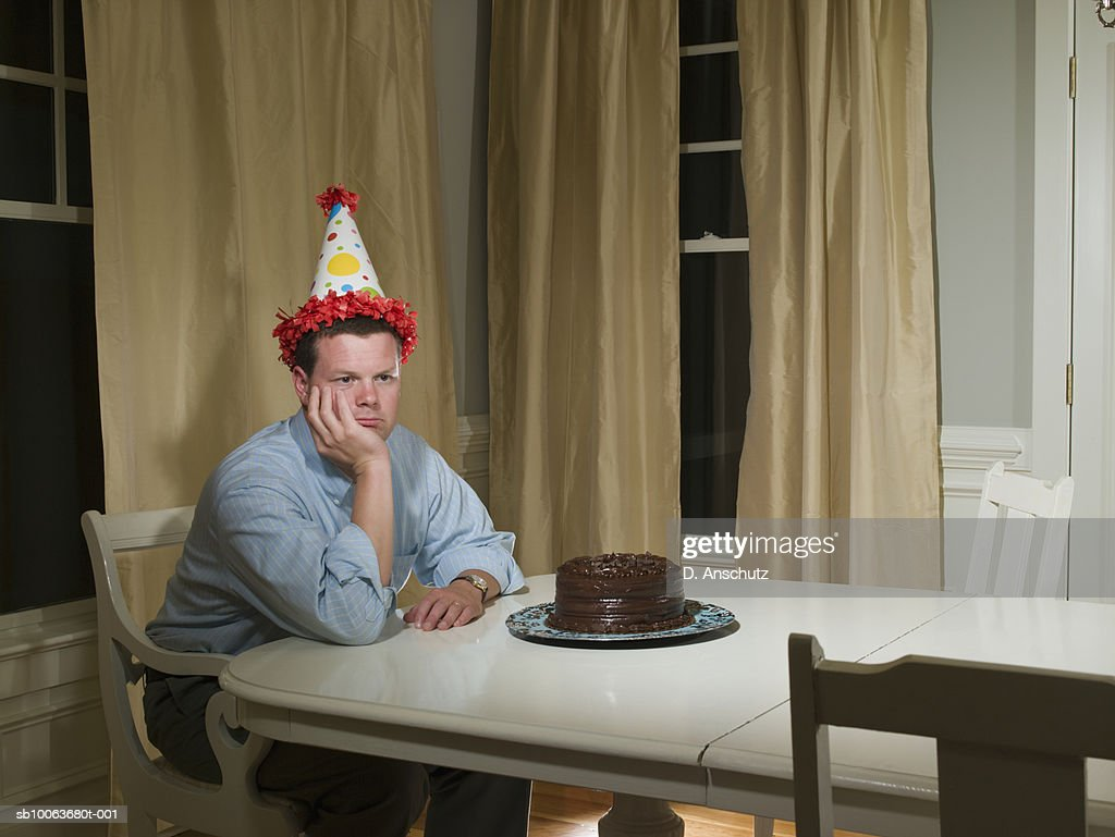 Mid adult man in party hat, sitting at table in front of birthday cake : Stock Photo