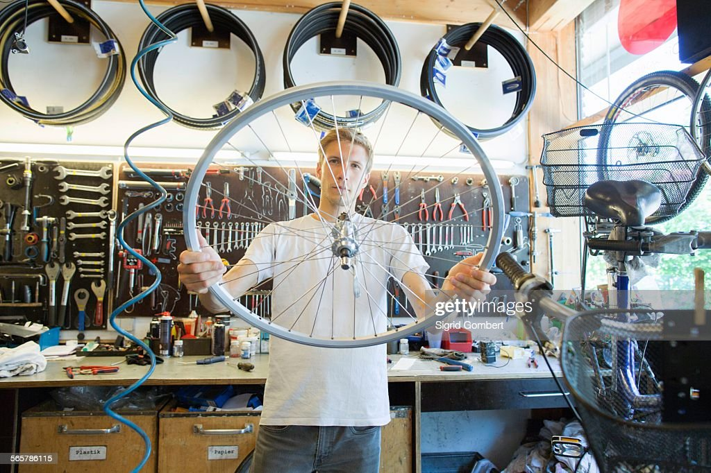 Mid adult man in repair shop looking through bicycle wheel : Stock-Foto
