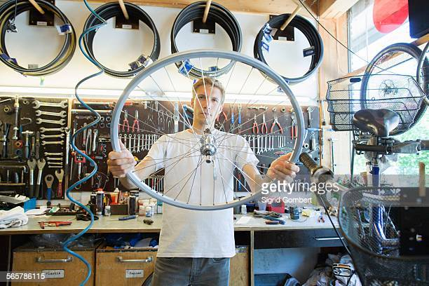 mid adult man in repair shop looking through bicycle wheel - sigrid gombert stock pictures, royalty-free photos & images