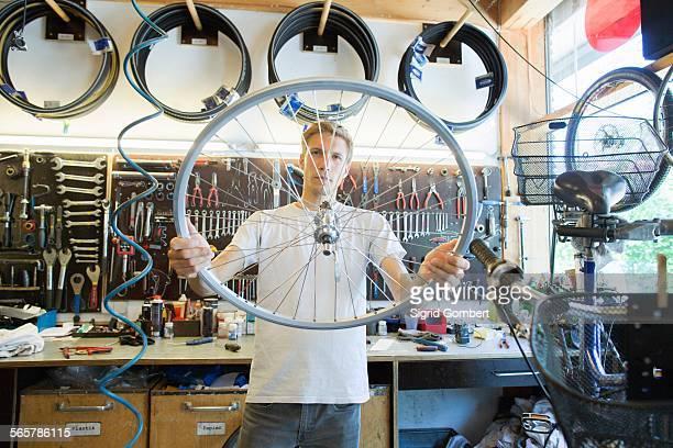 mid adult man in repair shop looking through bicycle wheel - sigrid gombert fotografías e imágenes de stock