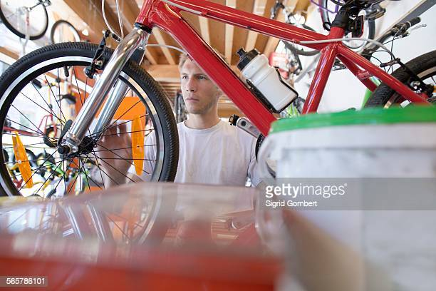 mid adult man in repair shop, view through bicycle frame - sigrid gombert stock pictures, royalty-free photos & images